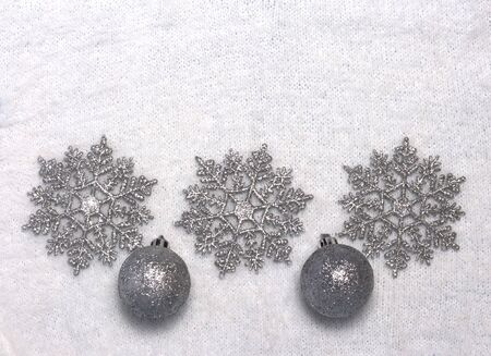 three silver snowflakes on a background of white fluffy winter Jersey with two Christmas balls.