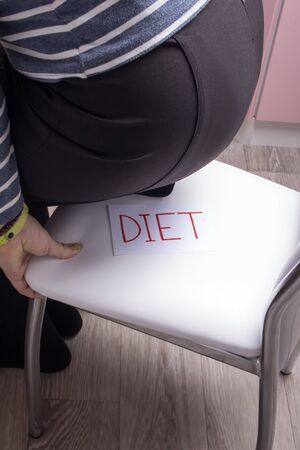 A woman sits on a chair where it says diet, the concept of going on a diet