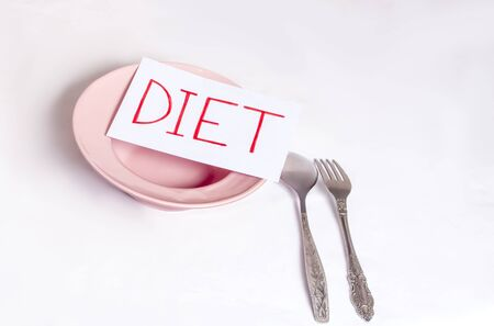 the concept of weight loss, on a white background, an empty plate with devices and the inscription diet Imagens - 133846395