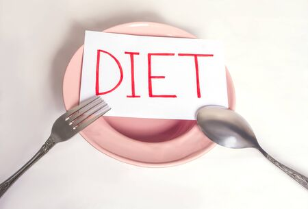 The word diet is written on a white sheet that lies on an empty plate with appliances Imagens - 133846399