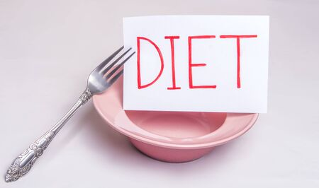 The word diet is written on a white sheet that lies on an empty plate with a table fork Imagens - 133846400