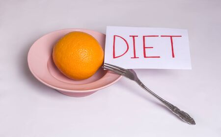 Nutrition concept Transition to proper nutrition Word diet on a white background with an orange in a plate Stockfoto