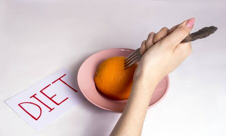 the girl reluctantly sits on a fruit diet, poking an orange with a fork Stockfoto