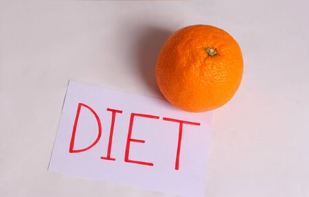 The word diet is written on a white sheet with an orange on a light background Imagens - 133846406