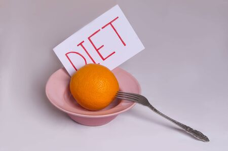 Transition to proper nutrition Word diet on a white background with an orange in a plate Imagens - 133846407