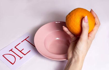 the girl reluctantly goes on a fruit diet, holding an orange over her pink plate Imagens - 133846584