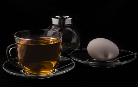 diet early Breakfast, a Cup of tea and an egg on a black background.