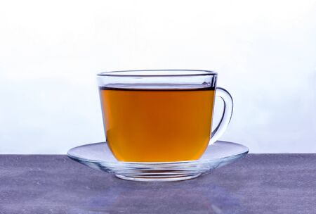 a transparent glass Cup with black tea stands at the light source. Imagens - 133846623