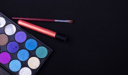 eyeshadow palette with brush and lipstick on black textured background. Imagens - 133846632