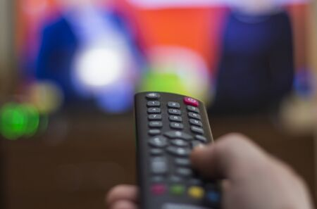 Hand holding TV remote control with TV in background. Imagens - 133846628