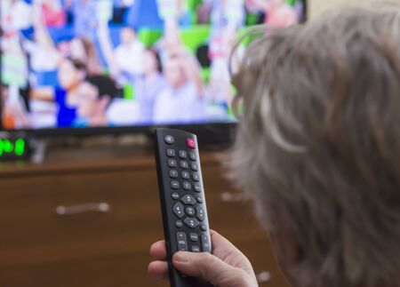 Rear view a gray-haired middle-aged woman controls the TV with a remote control. Imagens - 133846626