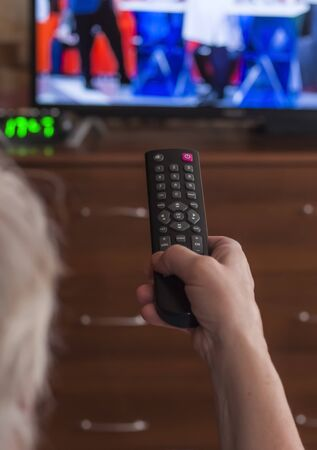 Rear view of a gray-haired woman, controls the TV with a remote control. Imagens - 133846627