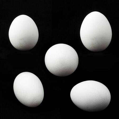 five white chicken eggs on black background. Imagens - 133846630