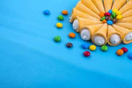 circle of white cakes in Waffle cones with colored candies with copy space. Imagens
