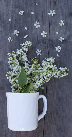 a bouquet of white flowers in a Cup on a wooden background, the concept of a morning Breakfast with a fragrant hot drink in a rustic . Imagens - 134930200