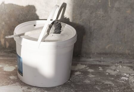 brush on a white round plastic paint container in the room where the repair is carried out. Imagens - 134932388