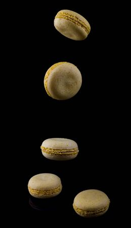 yellow macaroons fall down on a black background. Imagens - 134932535