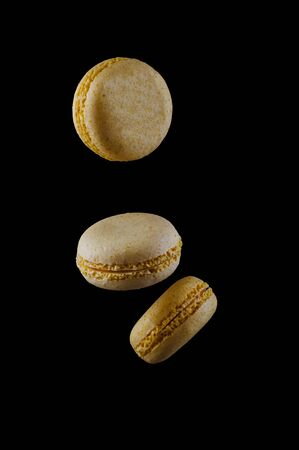 three yellow macaroons fall on a black background. Imagens - 134932127