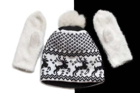 knitted white mittens and hat with Christmas pattern on black and white background flat lay. Imagens
