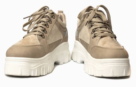warm beige sneakers with high soles isolated on white background. Imagens - 135399093