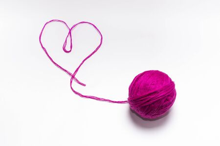 wool skein pink with a thread in the shape of a heart on a white background. Imagens - 135399096