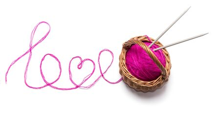 the word love consists of pink threads and tangles in a basket on a white background. Imagens - 135478371