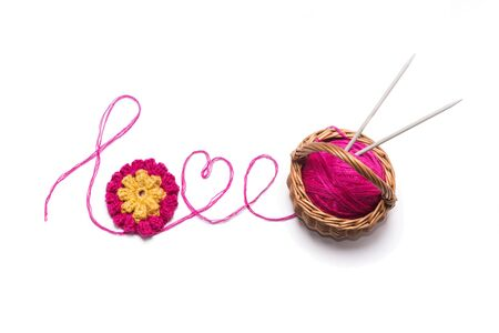 the word love consists of pink threads and a ball with spokes in a basket on a white background. Imagens - 135478377