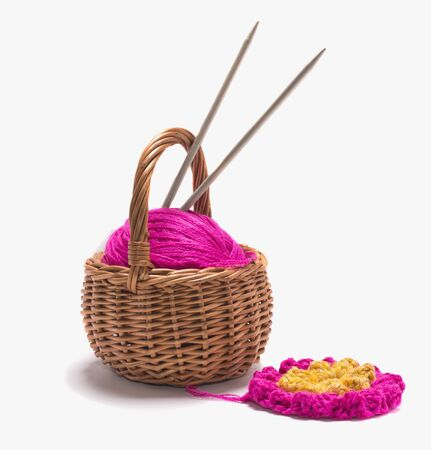 a ball of yarn with spokes in a basket on a white background. Imagens - 135478379
