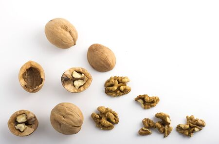 walnut shells and kernels with copy space on white background top view.