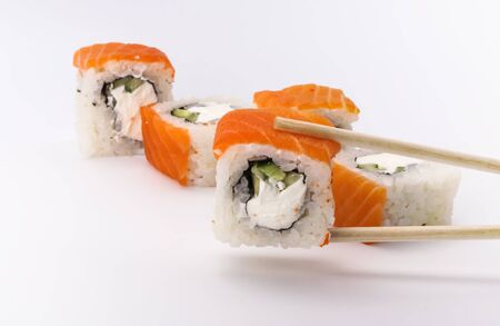 Delicious fresh sushi rolls with salmon and Philadelphia cheese on sticks on a white background.