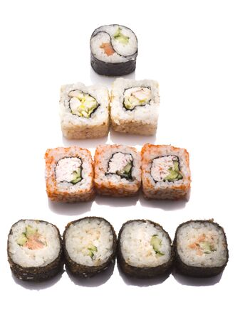 a variety of sushi rolls in the form of a Christmas tree on a white background. Imagens
