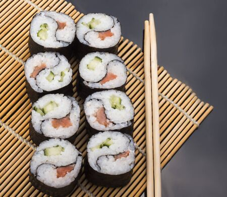 delicious Yin Yang sushi rolls on a Mat with sticks on a black background.