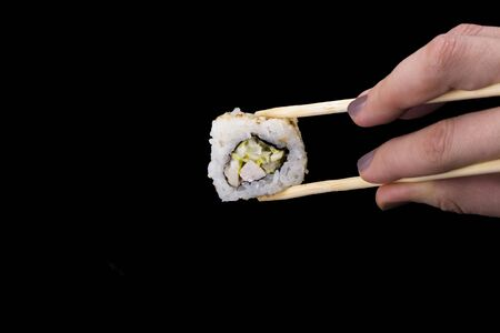 sushi rolls California in sesame on a black background.