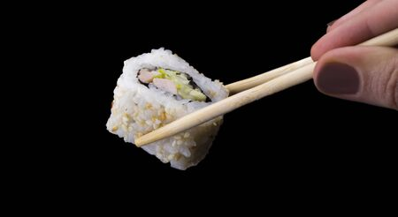 sushi rolls California in sesame on sticks on a black background.
