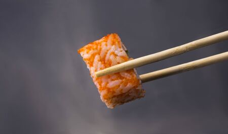 California sushi rolls on sticks on a gray background.