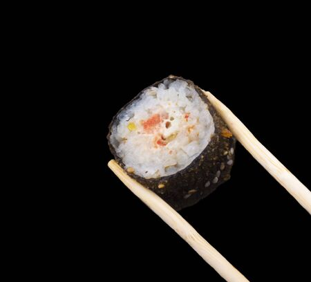 warm sushi rolls on sticks on a black background.