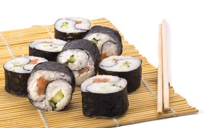 delicious Yin Yang sushi rolls on a Mat with sticks on a white background. Imagens