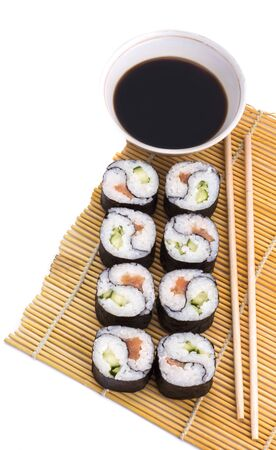 delicious Yin Yang sushi rolls on a Mat with sticks and soy sauce on a white background.