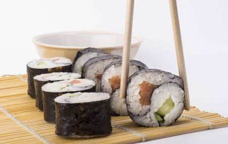 delicious Yin Yang sushi rolls on sticks on background and sushi roll on white background.