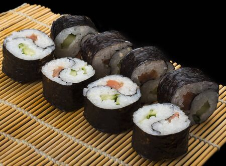 delicious Yin Yang sushi rolls on a Mat on a black background.