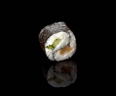 one delicious Yin Yang sushi rolls on a black background with reflection. Imagens