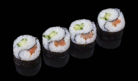 four delicious Yin-Yang sushi rolls on a black background with reflection. Imagens