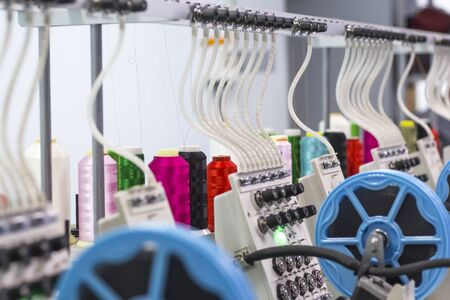 embroidery threads on a production embroidery machine. Imagens