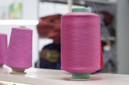 bobbins with pink elastic yarn on a knitting machine in the shop. Imagens