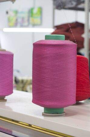 bobbins with pink elastic yarn on a knitting machine in the shop at work.