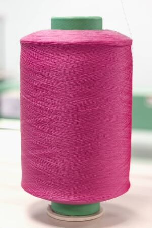 bobbin with pink elastic yarn on knitting machine. Imagens
