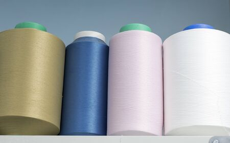colored elastic threads wound on bobbins are on the shelf in the production. Imagens