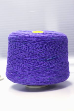 bobbin with purple yarn on a knitting machine.