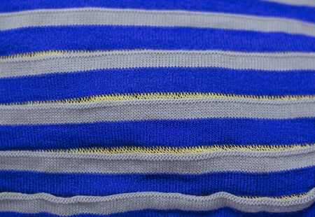 striped blue texture with grey, knitted fabric as background.