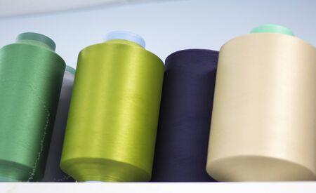 colored elastic threads wound on bobbins are on the shelf in the production view from below.